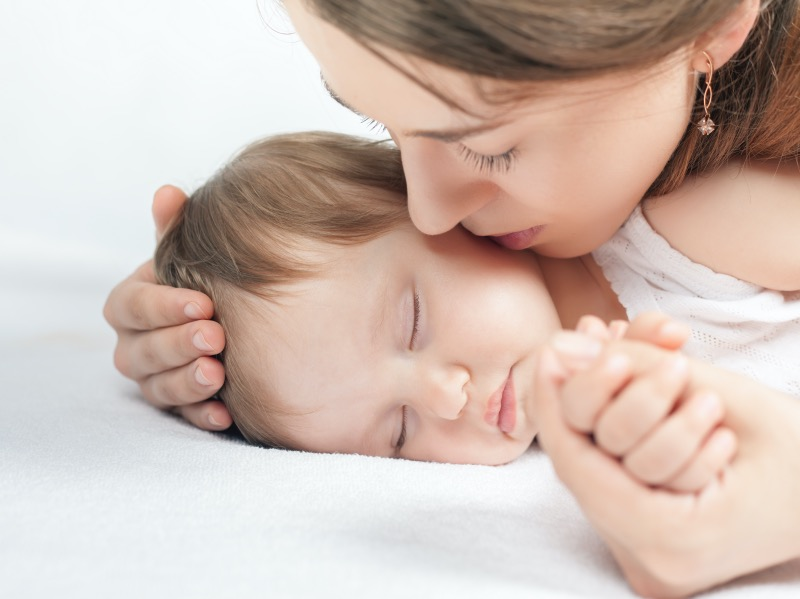 Mother kissing a baby. Care concept